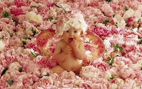 Ребенок с крыльями сидит в цветках