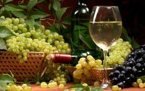 Белое вино и гроздья винограда