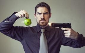 Мужчина стреляет в яблоко