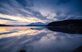Облака отражаются в горном озере