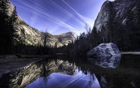 Mountain lake with a stone
