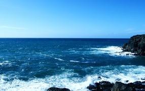 Синее море у черных камней