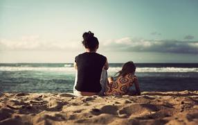 Женщина из дочкой сидят бери песке сверху берегу моря