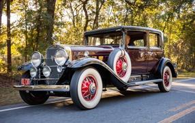 Стильный ретро автомобильчик Cadillac V16 бордового цвета