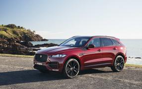 Бордовый колеса Jaguar F-Pace получай фоне океана