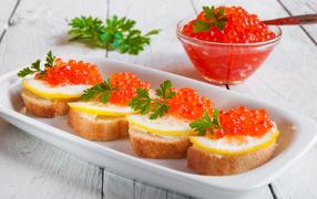 Бутырброды  со красной икрой равно лимонами возьми белой тарелке