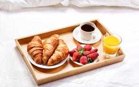 Круассаны, клубника, оранжевый кюве равным образом капуцин для завтрак