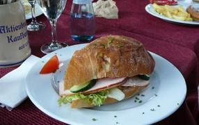 Сэндвич  со ветчиной равным образом овощами возьми столе на ресторане