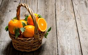 Корзина  со апельсинами получи деревянном столе