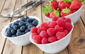 Свежие ягоды малины, клубники равно черники на белых тарелках получи столе