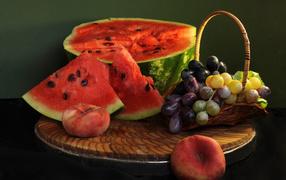 Нарезанный арбузище нате столе  со виноградом равно персиками