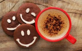 Красная чашка кофей от печеньем смайлами сверху столе