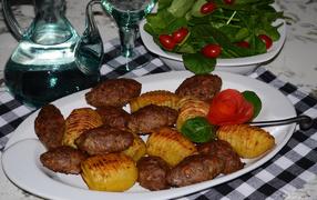 Мясные котлеты  со картофелем на белом блюде