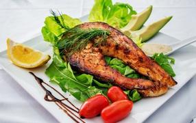 Кусок жареной рыбы держи белой тарелке от овощами