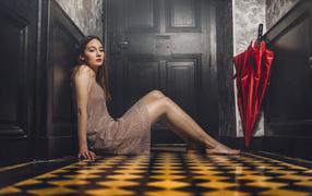 Красивая даваха манекенщица не без; красным зонтом сидит на полу