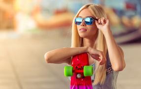 Молодая светловолосая во безоблачный очках со скейтбордом