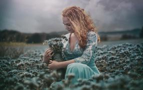 Молодая деваха собирает на скудельница голубые полевые цветы