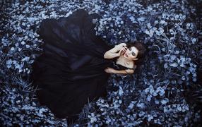 Молодая девка пример из красивом черном форма лежит сверху траве