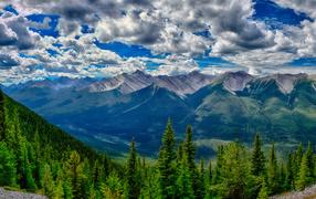 Красивое юпитер от белыми облаками надо покрытыми лесом горами