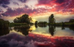 Красные облака отражаются на чистой воде реки