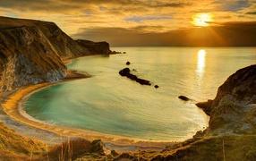 Скалы сверху берегу океана во лучах солнца для закате