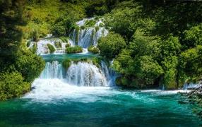 Бушующая голубая кипяток водопада у зеленых деревьев