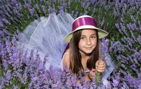 Девочка на шляпе лежит во фиолетовых цветах лаванды
