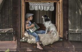 Маленький мальчонка из гармошкой сидит бери подоконнике от собакой
