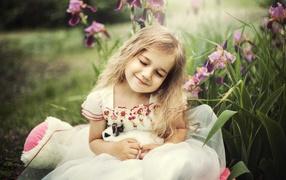 Маленькая девчура блондиночка держит во руках кролика