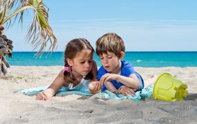 Маленькие мальчоночек да девчура играют бери песке у моря