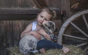 Маленькая кареглазая девчужка обнимает ягненка