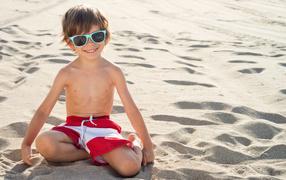 Маленький улыбающийся мальчуга на очках сидит в песке