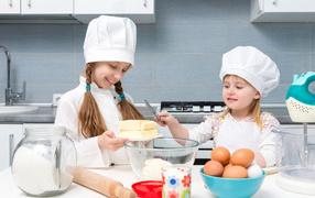 Две маленькие девочки для кухне готовят пирог