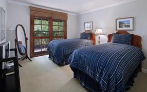 Две взрослые кровати во спальне вместе с деревянным окном