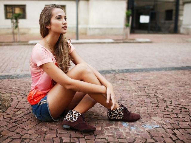 Брюнетка в шортах сидит на дороге