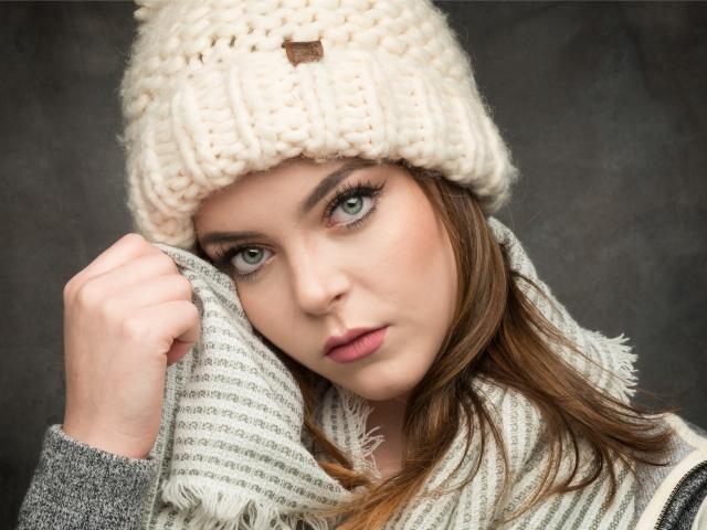 Красивая зеленоглазая девушка в белой вязаной шапке с шарфом