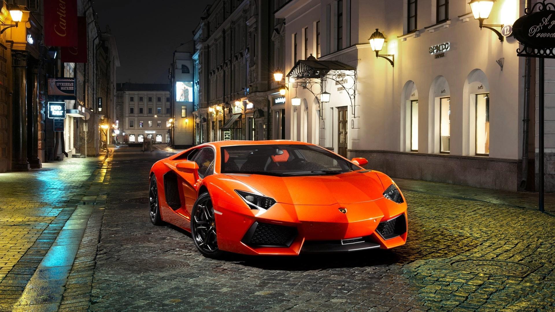 Orange Lamborghini Evening On An Empty Street With City Wallpaper