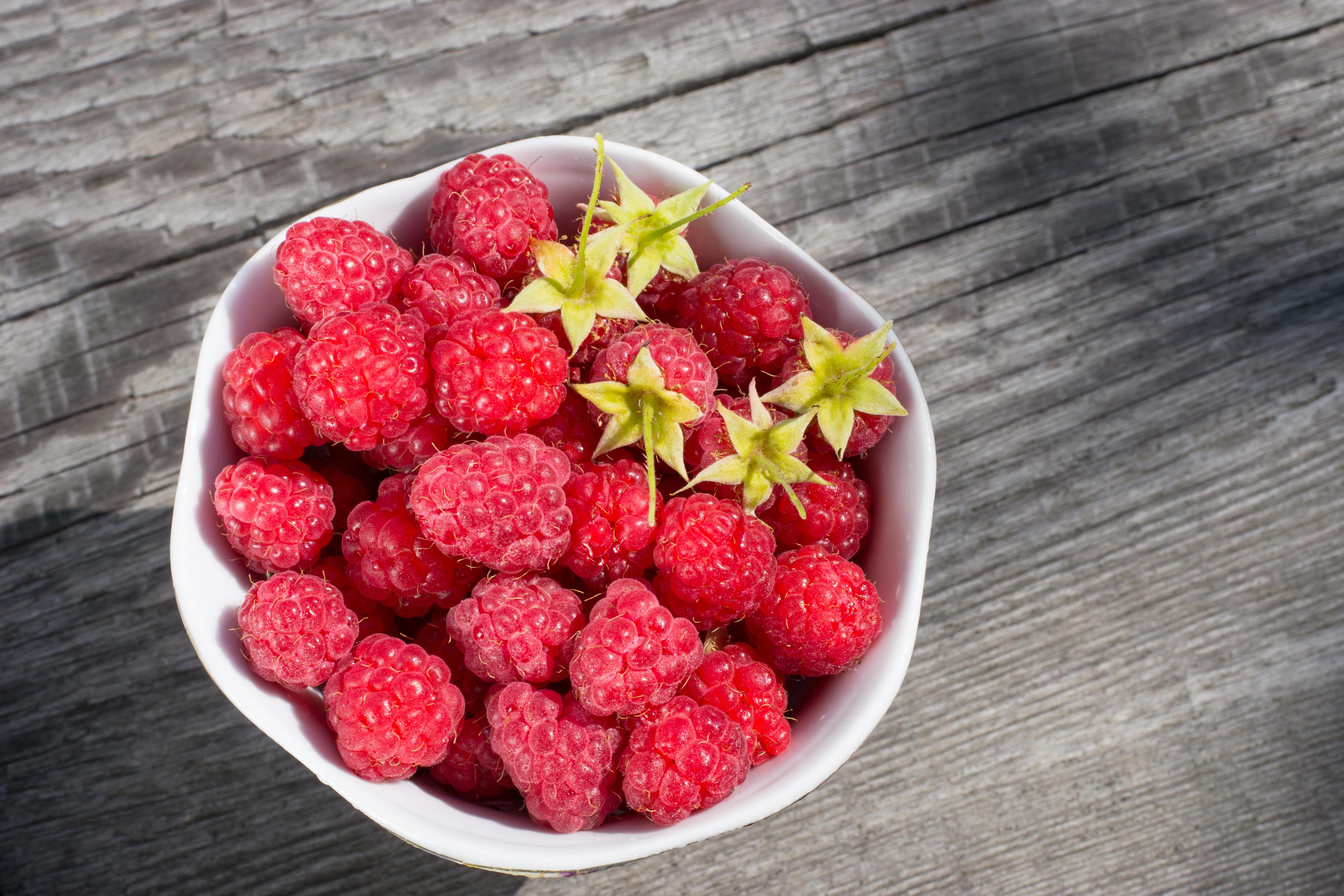 Appetizing juicy fresh raspberries in a white plate ...